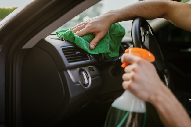 L'homme essuie l'intérieur de la voiture avec un chiffon, une station de lavage automatique des mains. industrie ou entreprise de lavage de voitures. un homme nettoie son véhicule de la saleté à l'extérieur