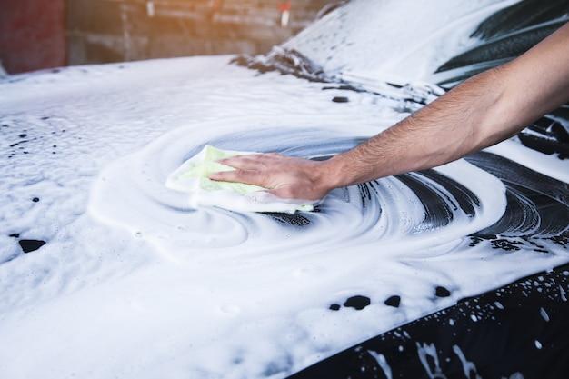 Un homme essuie la mousse sur la voiture avec un chiffon. lave-auto
