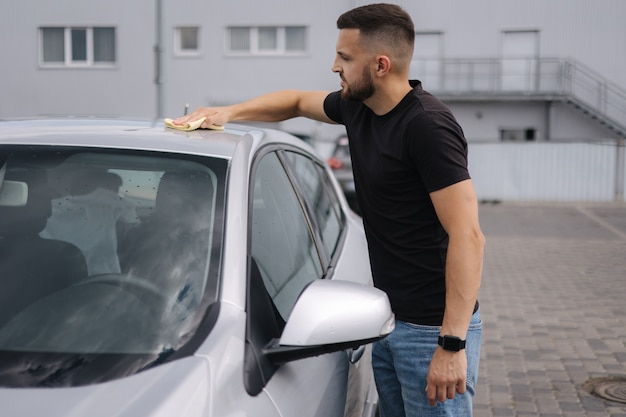 Un homme essuie le pare-brise de sa voiture avec un chiffon dans une salle d'exposition d'un lave-auto en libre-service