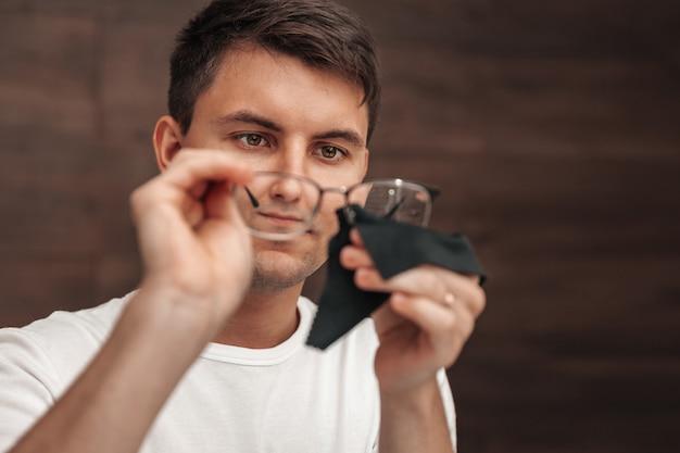 L'homme essuie ses lunettes avec un chiffon noir. photo en gros plan