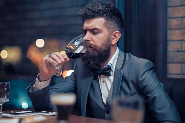 L'homme est assis au café, buvant de l'alcool, reste au restaurant avec un verre à vin