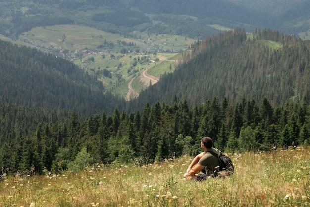 Un homme est assis au sommet d'une montagne se reposant et admirant le magnifique paysage