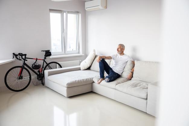 L'homme est assis sur un canapé blanc