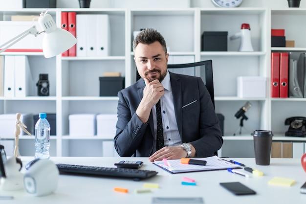 Un homme est assis sur une chaise dans le bureau à la table