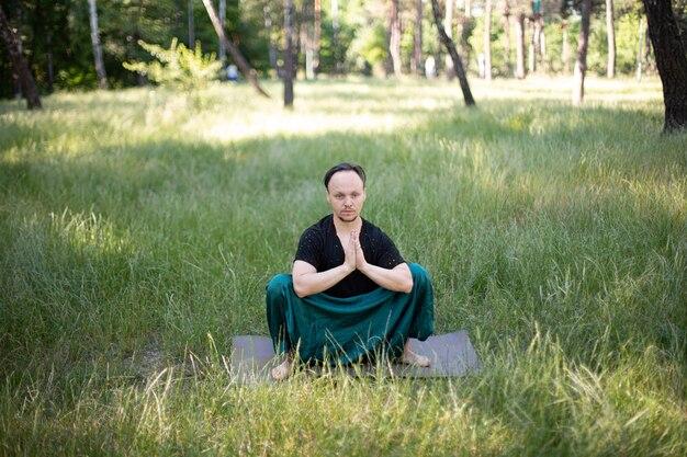 L'homme est assis dans un asana pratiquant le yoga dans le parc sur l'herbe verte. journée internationale du yoga