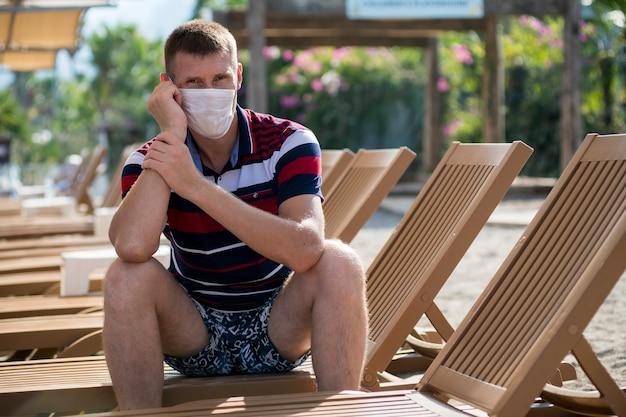 Un homme est assis dans une chaise longue portant un masque seul sur la plage pendant l'épidémie de grippe covid 19