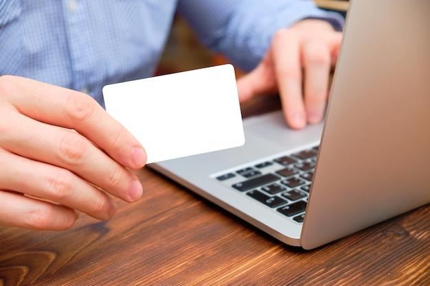 Un homme est assis dans une chemise sur un ordinateur portable et montre une carte