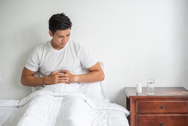 Un homme est assis dans son lit avec un mal d'estomac et appuie sur son ventre avec ses mains.