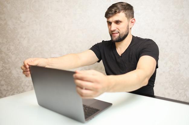 Un homme est assis devant un ordinateur portable