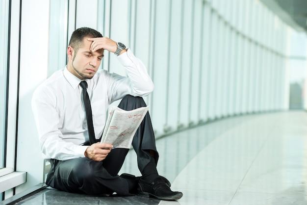 Un homme est assis avec un journal.