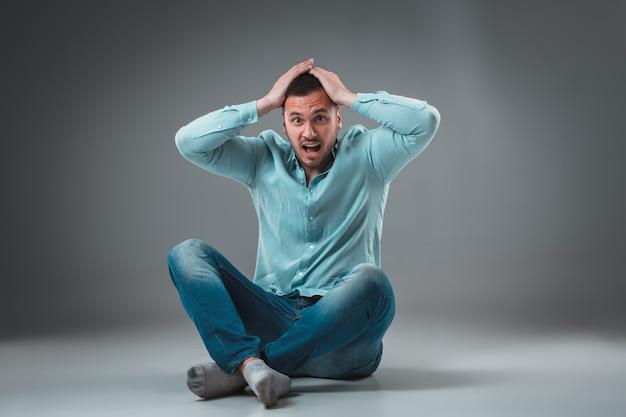 L'homme est assis par terre sur fond gris. homme montrant différentes émotions.