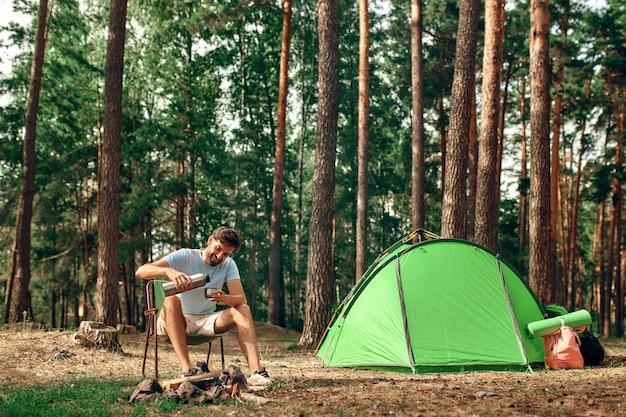 Un homme est assis près d'une tente près d'un feu de camp et verse du café ou du thé d'un thermos dans une forêt de pins pour le week-end. camping, loisirs, randonnées.