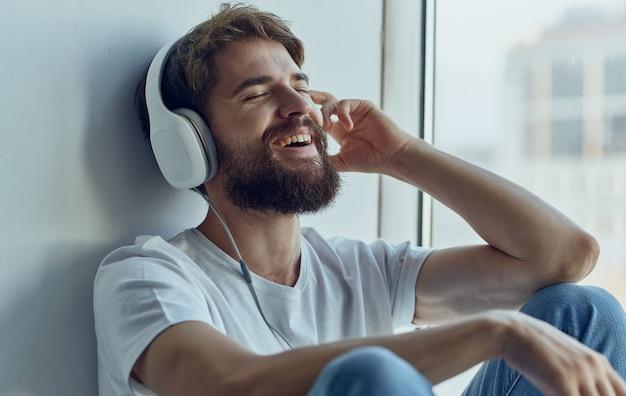 Un homme est assis sur un rebord de fenêtre portant des écouteurs et écoute de la musique
