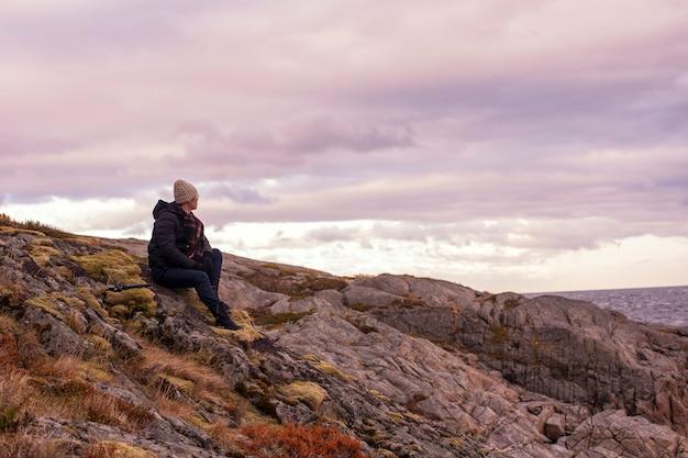 Un homme est assis sur le rocher de la montagne à lofoten, norvège