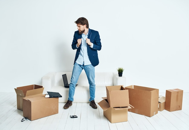 L'homme est assis sur le sol avec des boîtes en carton de choses en mouvement