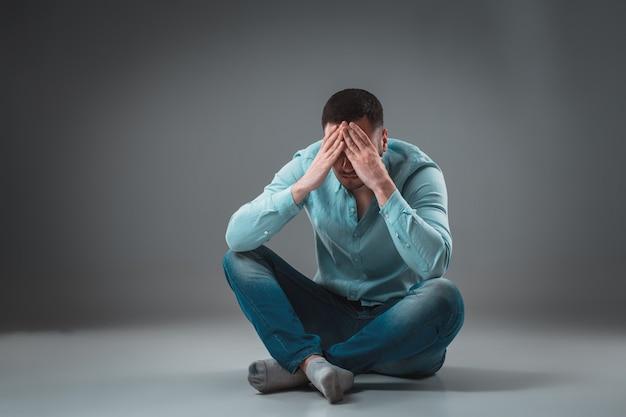 L'homme est assis sur le sol, isolé sur fond gris. homme montrant différentes émotions.