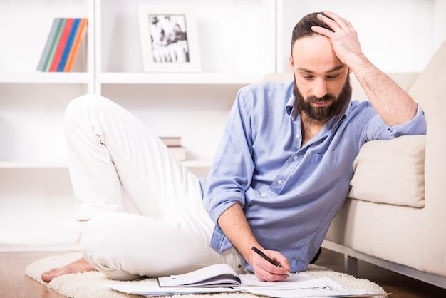 L'homme est assis sur le sol à la maison et travaille avec des documents.