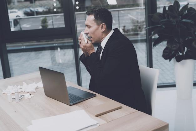 L'homme est assis sur son lieu de travail au bureau. il éternue