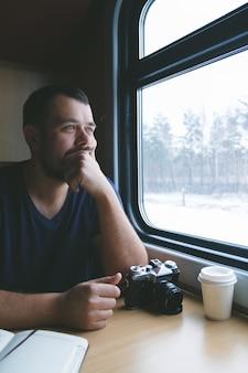 L'homme est assis à une table dans un train avec une caméra