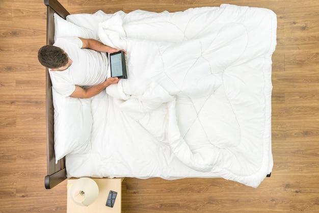 L'homme est assis avec une tablette sur le lit. vue d'en-haut