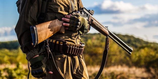 L'homme est à la chasse. homme chasseur. période de chasse, saison d'automne. homme avec une arme à feu. chasseur avec un sac à dos et un fusil de chasse. un chasseur avec un fusil de chasse et une forme de chasse pour chasser.