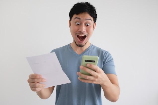 L'homme est choqué par la facture et le smartphone sur un mur isolé.