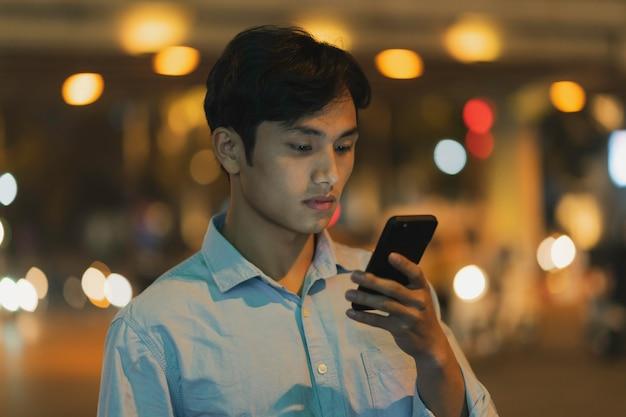 L'homme est debout à l'aide d'un téléphone portable dans le ciel le soir