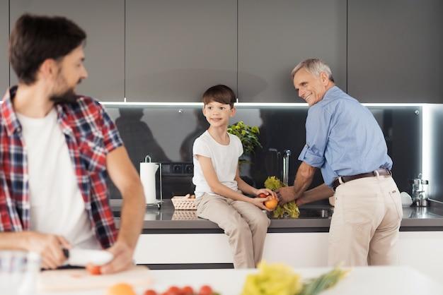 Un homme est debout dans la cuisine et coupe des légumes
