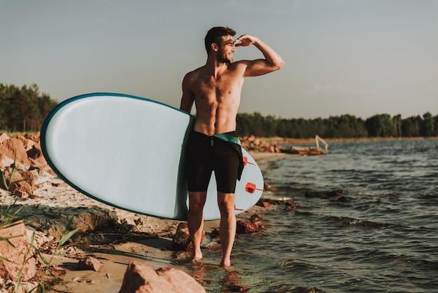 L'homme est debout sur la plage avec surf.