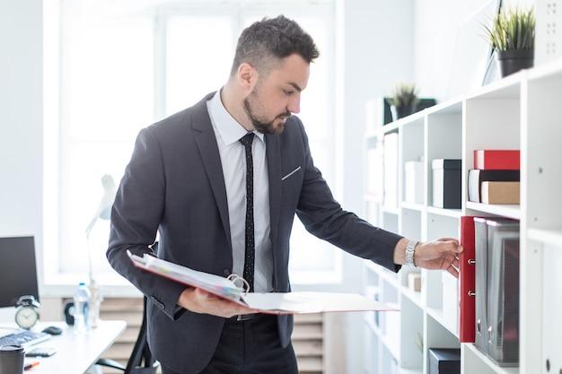 L'homme est debout près du rayonnage du bureau, tenant un dossier à la main et cherchant un dossier sur l'étagère.