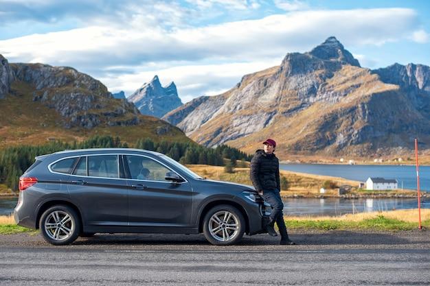 Un homme est debout avec la voiture dans l'île des lofoten, norvège