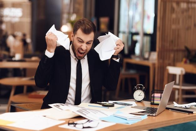 Un homme est déçu par la grande quantité de travail.