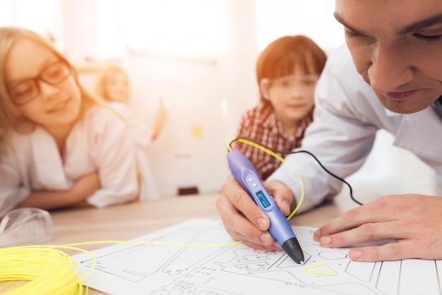 L'homme est enseignant, il montre aux enfants comment cela fonctionne.