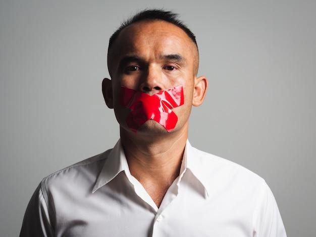 L'homme est réduit au silence avec du ruban adhésif rouge sur sa bouche scellée pour l'empêcher de parler. concept de liberté.
