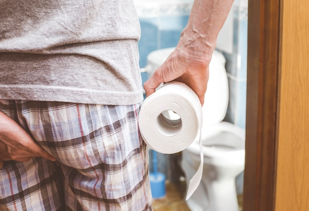 Un homme est titulaire de papier toilette. la diarrhée. concept de constipation.