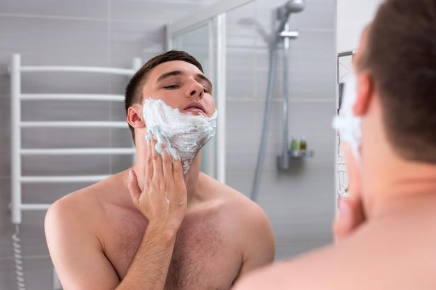 Homme étalant de la mousse pour se raser le visage debout devant un miroir dans la salle de bains carrelée moderne à la maison