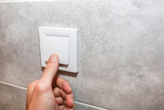 L'homme éteint les lumières. nouvelles prises sur le mur blanc. détails après rénovation. processus de restauration dans l'appartement.