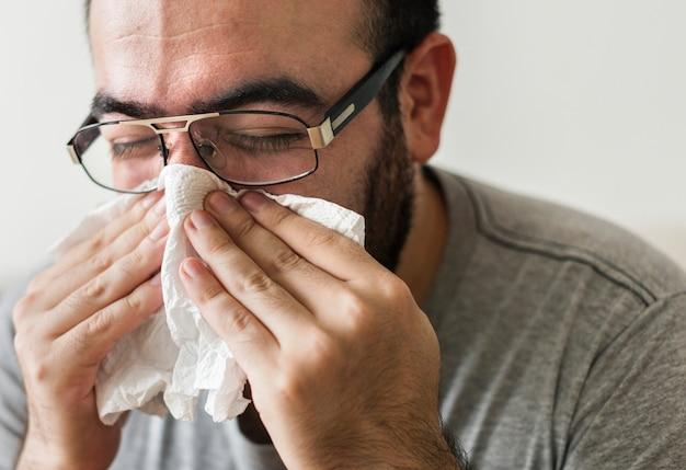 Homme éternuant dans un mouchoir en papier