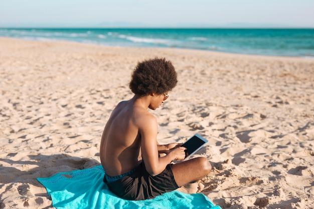 Homme ethnique à l'aide de tablette au bord de mer