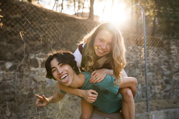 Homme ethnique avec fille sur le dos en train de rire à la caméra