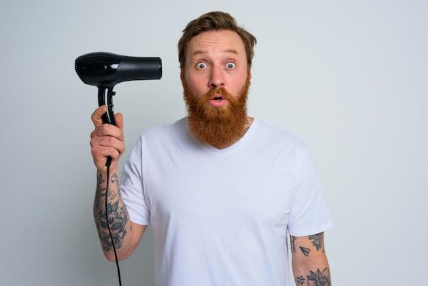 Un homme étonné à la barbe joue avec un sèche-cheveux comme une arme de poing