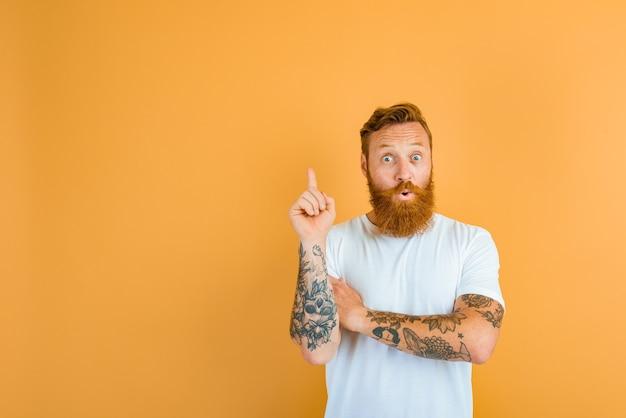 Homme étonné avec barbe, tatouage et t-shirt blanc