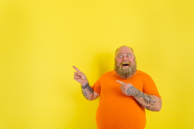 L'homme étonné avec la barbe et les tatouages est étonné et indique quelque chose