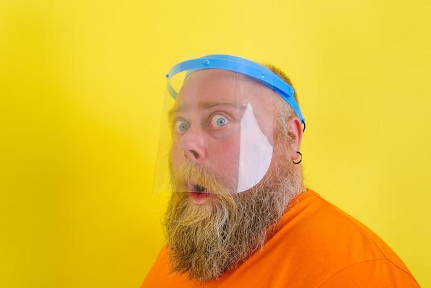 L'homme étonné avec la barbe et les tatouages porte un écran facial protecteur contre le covid