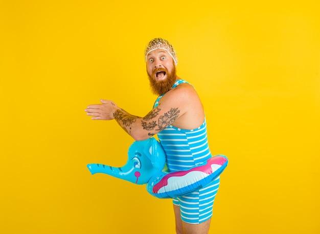 Un homme étonné avec une bouée de sauvetage et un bonnet pour les femmes étonnées est prêt pour l'été