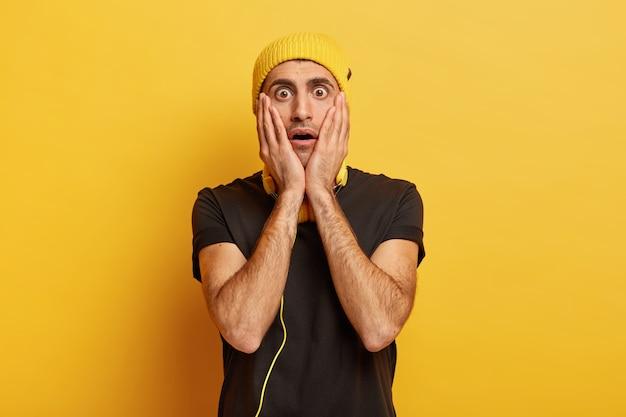 Un homme étonné choqué touche les joues avec les deux paumes, étant effrayé et peu sûr de lui