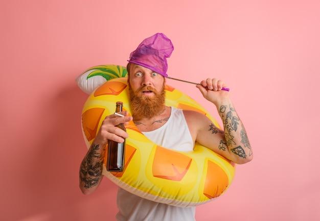 L'homme étonné est prêt à nager avec une bouée de sauvetage de beignet avec de la bière et une cigarette à disposition