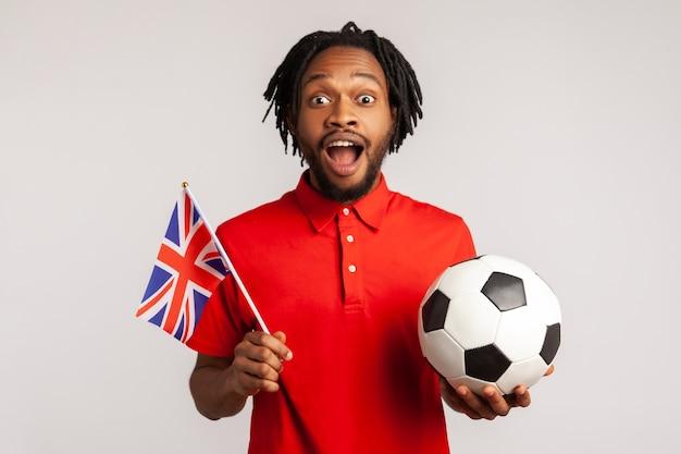 Homme étonné excité tenant le drapeau britannique et le ballon de football noir et blanc, ligue de football unie.