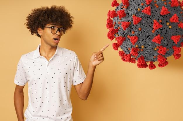 Un homme étonné avec des lunettes indique quelque chose avec la main