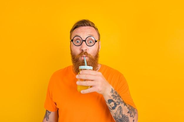 Un homme étonné de nerd avec des verres boit un jus de fruit